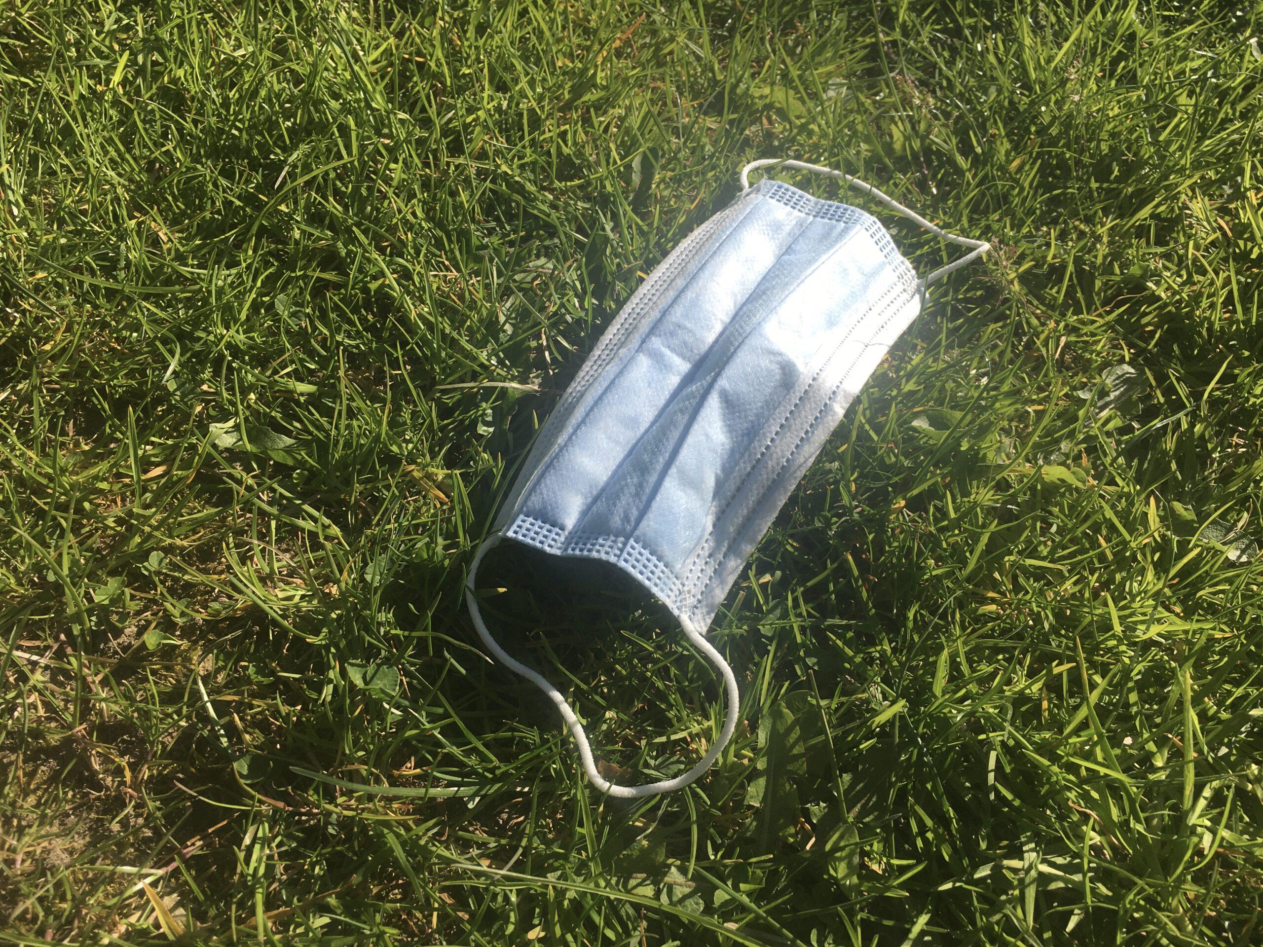 Eine OP-Maske liegt im Gras